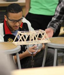 An engineering student works on an experiment to test load bearing.
